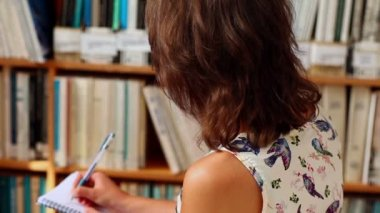 Young female student writing in library — Stock Video