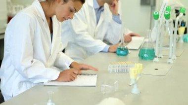 Estudiante de química mirando hacia arriba de su trabajo y sonriendo — Vídeo de stock