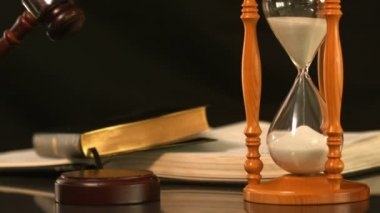 Gavel dropping on sounding block beside hourglass and bible — Stock Video