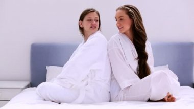 Girls wearing bathrobes chatting on bed — Stock Video