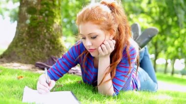Pretty young student lying on the grass making notes — Stock Video