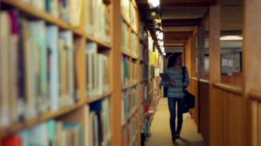 Student walking through the library — Stock Video