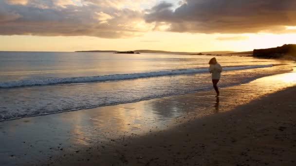 Femme qui court le long de l'eau au coucher du soleil — Vidéo