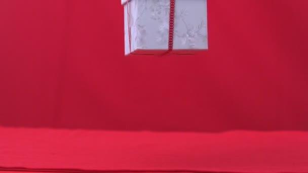 Regalo de Navidad cae y rebota sobre fondo rojo — Vídeo de stock