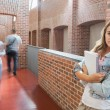 Student leaning against wall in the corridor looking at camera — Stock Photo #38453487