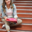 Happy student sitting on stairs looking at camera — Stock Photo