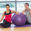 Young woman and man with fitness ball sitting at gym — Stock Photo #38453625