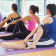 Class doing the half spinal twist pose on mats at yoga class — Stock Photo #38453711