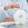 Mid section of a man putting some coins into a piggy bank — Stock Photo #38453911
