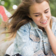 Стоковое фото: Smiling young student studying on grass