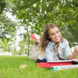 Foto Stock: Cheerful young student studying on grass