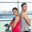 Serious young woman and man standing back to back in gym — Stock Photo #38454973