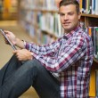 Smiling young student sitting on library floor using tablet — Stockfoto #38455219