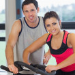 Trainer watching woman work out at spinning class — Stock Photo #38455247