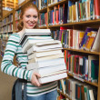 Smiling student holding heavy pile of books standing in library — Stock Photo