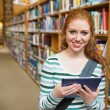 Cheerful student using tablet standing in library — Stock Photo