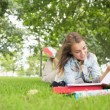 Stock Photo: Happy young student studying on the grass