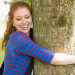 Laughing redhead hugging a tree — Stock Photo