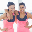 Two fit young women smiling in a bright exercise room — Stock Photo