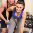 Trainer helping young womwith dumbbells in gym — Photo #38456229