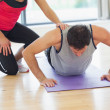 Female trainer assisting man with push ups in gym — Stock Photo #38456405