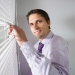 Businessman peeking through blinds in office — Stock Photo