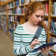 Focused student using tablet standing in library — Stock Photo #38456519