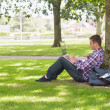 Young student using laptop outside — Foto de stock #38456521