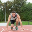Young man ready to race on running track — Stock Photo #38456587