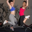 Two fit young women jumping in the gym — Stock Photo #38456899