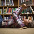 Pretty student lying on library floor reading book — Stock Photo #38456921