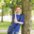 Cheerful student leaning against a tree talking on the phone — Stock Photo #38456971