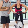 Trainer watching woman work out at spinning class — Stock Photo #38457087