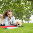 Foto Stock: Happy student lying on grass studying