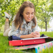 Pretty smiling student lying on grass sending text — Stock Photo #38457181
