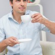 Thoughtful young man drinking tea at home — Stockfoto