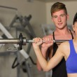 Male trainer helping fit woman to lift the barbell in gym — Stock Photo