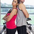 Serious young woman and man standing back to back in gym — Stock Photo #38457539