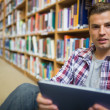 Young student sitting on library floor using tablet — Stockfoto #38457635