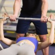 Trainer helping womto lift barbell bench press in gym — Photo #38457759