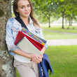 Happy student leaning on tree holding her books — Stock Photo #38457891