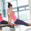 Two fit women performing step aerobics exercise in gym — Stock Photo #38458207