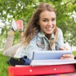 Smiling student lying on grass studying with her tablet pc — Stok Fotoğraf #38458445