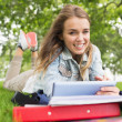 Foto Stock: Smiling student lying on grass studying with her tablet pc