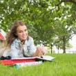 Foto Stock: Happy young student lying on grass studying
