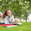 Stock Photo: Happy young student lying on grass studying