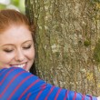 Smiling redhead hugging a tree — Stock Photo