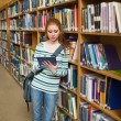 Focused student using tablet leaning on shelf in library — Stock Photo #38458697