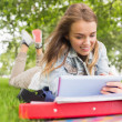 Foto Stock: Happy student lying on grass studying with her tablet pc