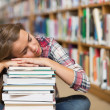 Stock Photo: Napping student sitting on library floor leaning on pile of books